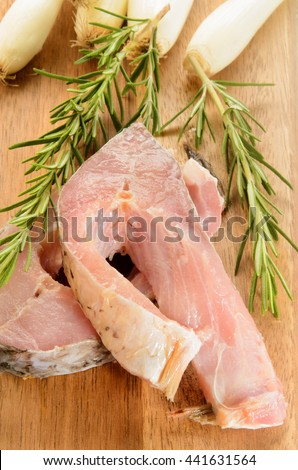 raw carp steak with rosemary and spring onions on wooden board - stock photo