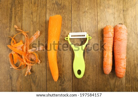 Raw carrots and peeler on wooden table