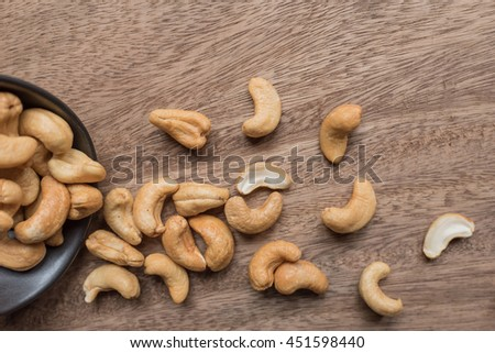 Raw cashew nuts in bowl on textured wooden background, table top view