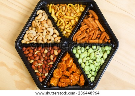 Raw cashews and peanuts with variety of snacks in black cans. Close up - stock photo