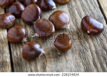 Raw chestnuts on rustic wooden board