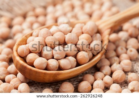 Raw chick peas organic nutrition super food in wooden spoon close up on vintage textile background - stock photo