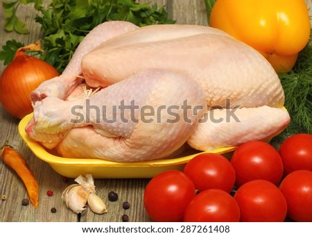 Raw chicken and vegetables on a wooden table - stock photo