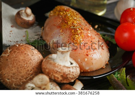 Raw chicken breast fillet with cherry tomatoes, pepper and mushrooms covered with spices for cooking on dark wooden table, closeup