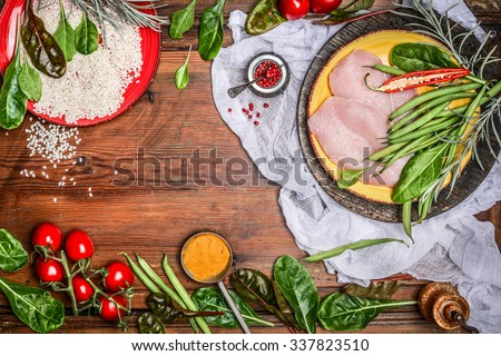 Raw chicken breast with rice and fresh organic vegetables ingredients for healthy cooking on rustic wooden background, top view, frame. Diet food or sports nutrition concept.  - stock photo