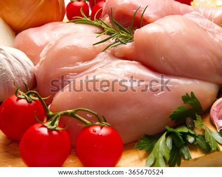Raw chicken breasts with vegetables on cutting board  - stock photo