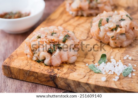 Raw chicken cutlets with herbs and seasoning on olive wood background, closeup, selective focus - stock photo