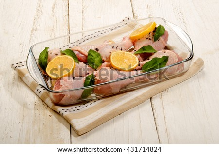 raw chicken drumstick with sage and lemon slice in a glass bowl - stock photo