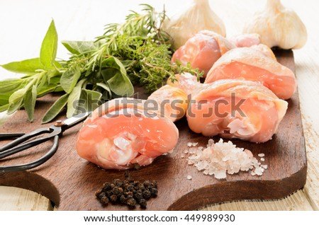 raw chicken drumsticks fresh herbs from the garden, coarse sea salt and peppercorns on a wooden board  - stock photo