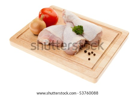 Raw chicken drumsticks on board isolated on white background - stock photo