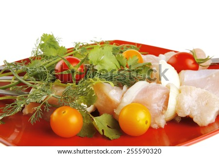 raw chicken kebabs on red served with tomatoes - stock photo