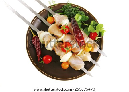 raw chicken kebabs served on skewers with vegetables - stock photo