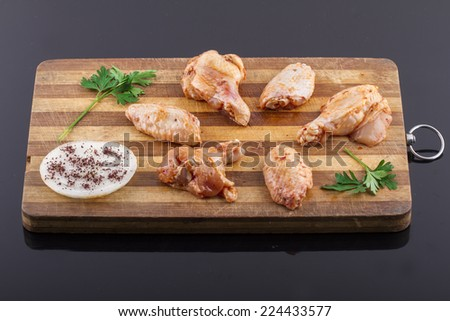 raw chicken legs and chicken wings on a plate