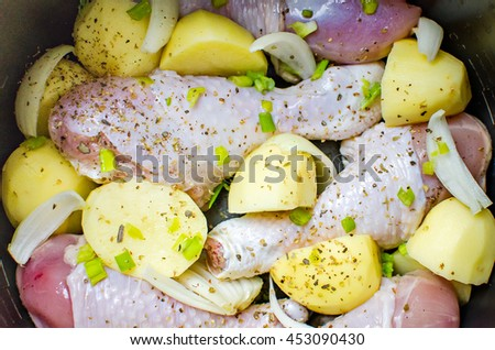 raw chicken legs and potatoes with onion and spices  - stock photo