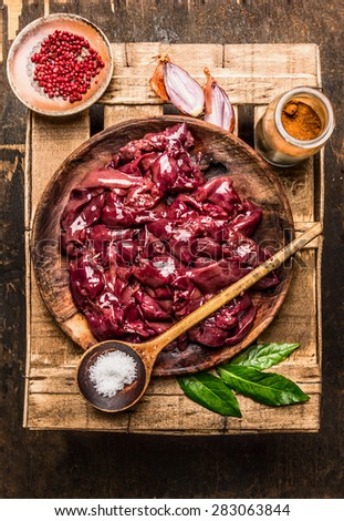 Raw chicken liver in rustic bowl with herbs and spices ingredients for cooking, composing, top view - stock photo