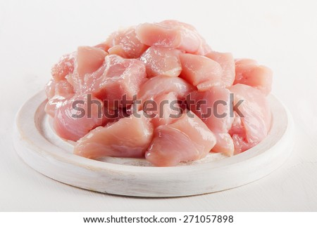 Raw chicken meat on  white wooden cutting board. Selective focus - stock photo