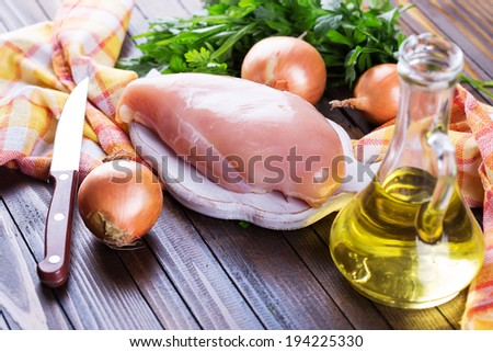 Raw chicken meat on wooden board on table. Selective focus, horizontal. - stock photo
