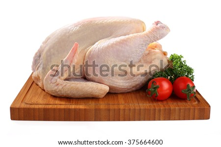 Raw chicken on cutting board with tomatoes  - stock photo