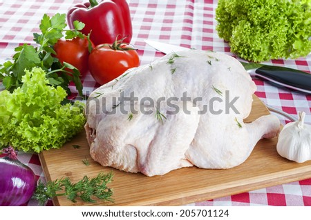 Raw chicken on wooden board with knife