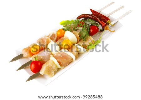 raw chicken shish kebab on long white plate