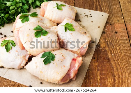 Raw chicken thighs with parsley on wooden table - stock photo