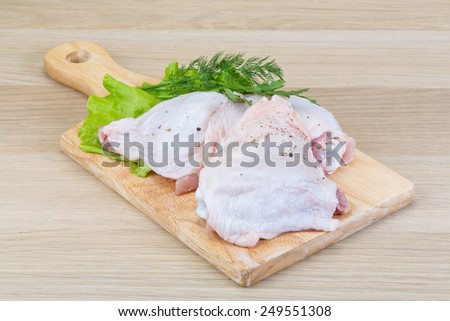 Raw chicken thighs with salad leaves and ruccola - stock photo