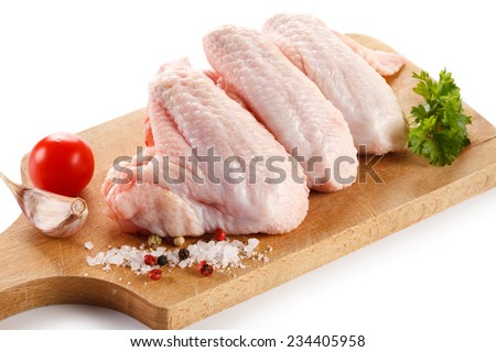 Raw chicken wings on cutting board on white background - stock photo