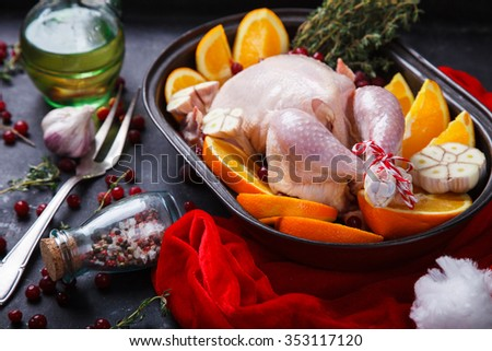 Raw chicken with oranges and cranberries for Christmas.Thanksgiving Dinner. selective focus. - stock photo