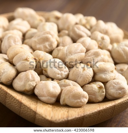 Raw chickpeas or garbanzo beans on small wooden plate, photographed with natural light (Selective Focus, Focus one third into the image) - stock photo