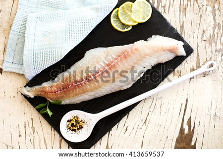 raw cod fillet over slate plate
