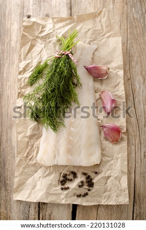raw cod fillet with dill, garlic and pepper on brown kitchen paper - stock photo