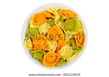 Raw colored tortellini in a bowl, on a white background - stock photo