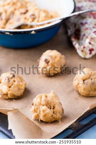 Raw cookie dough on a baking tray with parchment paper, selective focus - stock photo