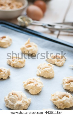 Raw cookie dough on a baking tray with parchment paper, selective focus
