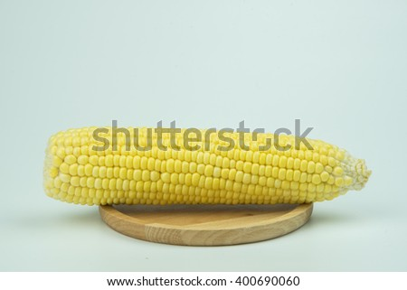 Raw corn on a wooden plate On  white background. - stock photo