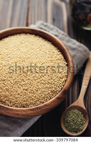 Raw couscous in a bowl on a wooden table Vegan food