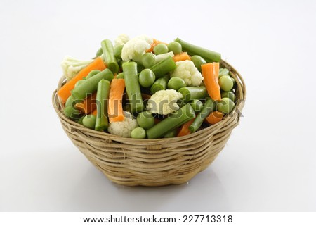 Raw cut mix vegetables in cane container along with chopping board, Carrot, Cauliflower, French beans, Green Peas - stock photo