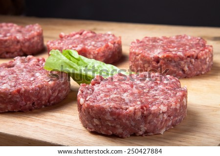 Raw cutlet of minced meat on a wooden cutting board. - stock photo