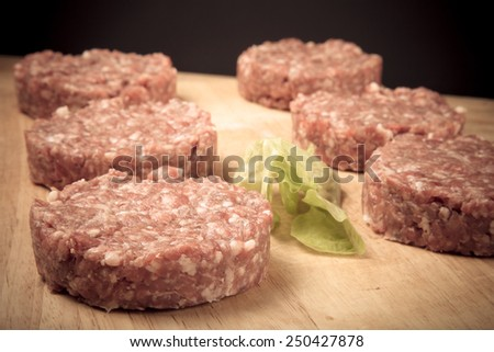 Raw cutlet of minced meat on a wooden cutting board. Toned. - stock photo