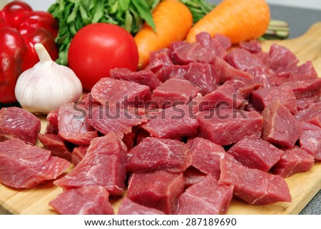 Raw cutting beef with vegetables on wooden plate  - stock photo