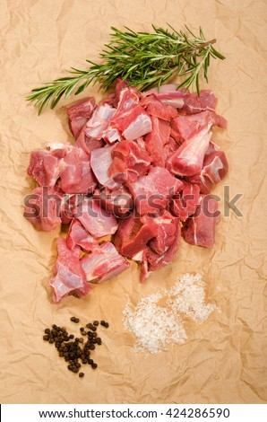 raw deer goulash with rosemary, pepper corn and kosher salt on brown kitchen paper - stock photo