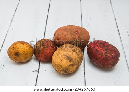 raw dirty potato isolated on a white wooden background  - stock photo