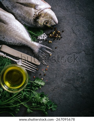 Raw dorada fish with ingredients and blank space on the right side  - stock photo