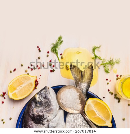 raw dorado fish with oil and lemon on white wooden background, top view, close up - stock photo
