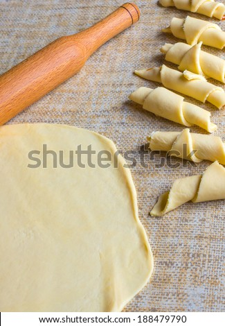 Raw dough and some croissants ready for baking - stock photo