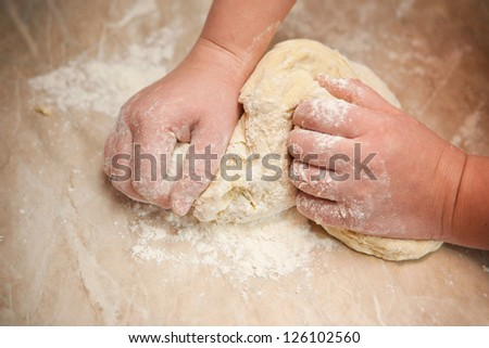 raw dough chef kneads his hands on the table - stock photo