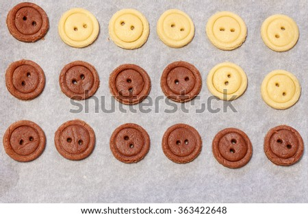 Raw dough. Yellow and brown cookies buttons. Cooking - stock photo