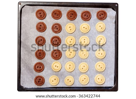 Raw dough. Yellow and brown cookies buttons on sheet pan. Cooking. Isolated white background - stock photo