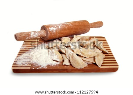 Raw Dumplings on cutting board on wooden background close-up