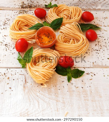 raw egg and noodles with spices on wooden table - stock photo
